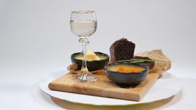 Fresh red caviar with basil and butter on bread in studio. Bred with red caviar with wine glasses on background. Cold. Russian vodka with ice and small snacks Stock Image