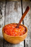 Fresh red caviar in a wooden bowl with a spoon. On a rustic background Royalty Free Stock Photo