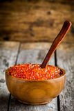Fresh red caviar in a wooden bowl with a spoon. On a rustic background Stock Photos