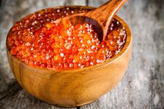 Fresh red caviar in a wooden bowl with a spoonful closeup Royalty Free Stock Photo
