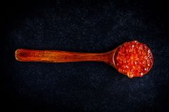 Fresh red caviar in a wooden spoon. On a black background Royalty Free Stock Photo