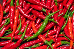 Fresh red, cayenne chili peppers and one green pepper. Fresh cayenne red chili peppers and one green chilli pepper in middle stock photo