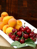 Fresh red cherries and apricots Stock Photography