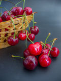 Fresh red cherries on a basket on black. Background Stock Photos