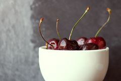 Fresh red cherries in a cup. Berries with stalks, juicy and healthy.  Royalty Free Stock Images