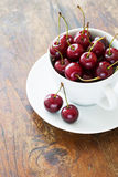 Fresh red cherries in a cup. On a wooden table Royalty Free Stock Photography