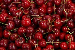 Fresh red cherries on retail market close up. Heap of fresh red ripe sweet black cherry berries on retail market stall display, close up, high angle view stock photography