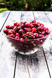 Fresh Red Cherry berries in glass bowl on wooden rustic  backgro Royalty Free Stock Photos