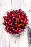 Fresh Red Cherry berries in glass bowl on wooden rustic  backgro Stock Photography
