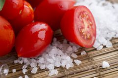 Fresh red cherry tomato and rock sea salt on rustic wooden background. Healthy vegetable, ingedient. Organic stock images