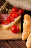 Fresh red cherry tomato between rolls and baguette Stock Photos