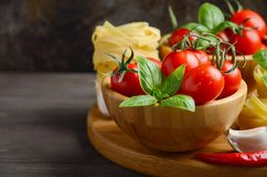 Fresh red cherry tomatoes with raw pasta, basil, chili pepper and garlic for Italian food. Selective focus, copy space Stock Images