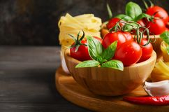 Fresh red cherry tomatoes with raw pasta, basil, chili pepper and garlic for Italian food. Selective focus, copy space Royalty Free Stock Image