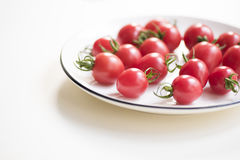 Fresh red cherry tomatoes. On a white plate on white Royalty Free Stock Images