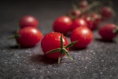 Fresh red cherry tomatoes on dark stone background royalty free stock image