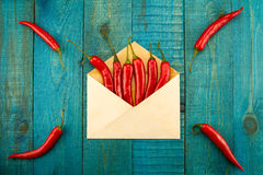 Fresh red chili pepper in a blue envelope on wooden background Stock Image