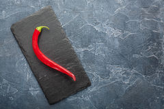 Fresh red chili peppers on a dark stone with expressive texture Stock Photography