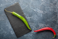 Fresh red chili peppers on a dark stone with expressive texture Stock Photos