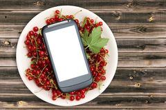 Fresh Red currant in plate and smartphone with a white screen mock up on wood table, top view, copy space. Technology Internet in. Agriculture. Applications for Royalty Free Stock Photography