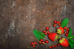 Fresh red currant and strawberry with mint. On a old black background. Top view. Close-up. Fresh red currant and strawberry with mint. On a old black background Stock Photos