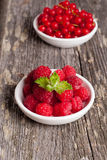Fresh red currant and sweet raspberries on wooden table. Vertical Stock Photo