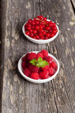 Fresh red currant and sweet raspberries on wooden table Stock Images