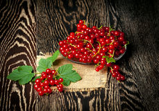Fresh red currants with leaves on wooden background. Close up Stock Photography