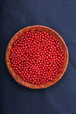 Fresh and red currants in a wooden crate, close-up. Healthy, ripe, raw and bright red berries on a dark blue fabric. Summer. Royalty Free Stock Photography
