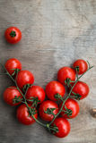 Fresh red delicious cherry tomatoes  on an old wooden tabletop b Stock Photo