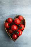 Fresh red delicious tomatoes  in heart-shape plate. Close -up of fresh red delicious tomatoes    in heart-shape plate on an  old wooden tabletop Stock Images