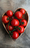 Fresh red delicious tomatoes  in heart-shape plate Stock Image