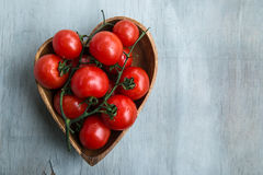 Fresh red delicious tomatoes. In the heart shape wooden plate on an wooden tabletop with place for text Stock Image