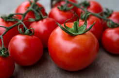 Fresh red delicious tomatoes  on an old wooden tabletop backgrou Stock Images