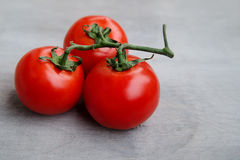 Fresh red delicious tomatoes  on an old wooden tabletop background Royalty Free Stock Photo