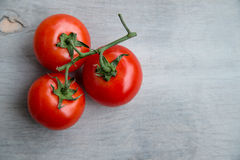 Fresh red delicious tomatoes on an old wooden tabletop Royalty Free Stock Images