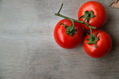 Fresh red delicious tomatoes on an old wooden tabletop Royalty Free Stock Photos