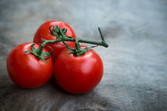 Fresh red delicious tomatoes  on an  old wooden tabletop Royalty Free Stock Image