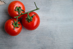 Fresh red delicious tomatoes on an old wooden tabletop Royalty Free Stock Photography