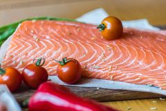 Fresh red fish salmon fillet and tomatoes, lime and chili pepper. Are ready for cooking Royalty Free Stock Images