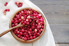 Fresh red forest cranberry in a round bowl with a wooden spoon on white linen fabric on a table surface Stock Images