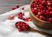 Fresh red forest cranberry in a round bowl with a wooden spoon on white linen fabric on a table surface Royalty Free Stock Photography
