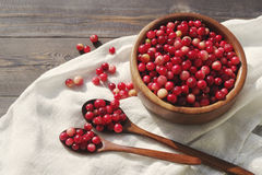 Fresh red forest cranberry in a round bowl with a wooden spoon on white linen fabric on a table surface Stock Photos