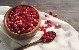 Fresh red forest cranberry in a round bowl with a wooden spoon on white linen fabric on a table surface Royalty Free Stock Image