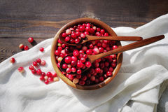 Fresh red forest cranberry in a round bowl with a wooden spoon on white linen fabric on a table surface Royalty Free Stock Photo