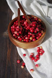 Fresh red forest cranberry in a round bowl with a wooden spoon on white linen fabric on a table surface Stock Photography