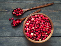 Fresh red forest cranberry in a round bowl with a wooden spoons Royalty Free Stock Photography
