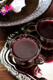 Fresh red grape juice and flowers. On wooden rustic table Stock Image