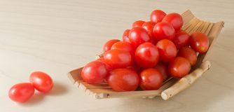 Fresh Red Grape Tomatoes on Small Boat. Vegetable, Ripe Red Grape Tomatoes or Cherry Tomatoes on A Small Wooden Boat Stock Photography