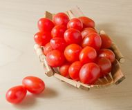 Fresh Red Grape Tomatoes on Small Boat. Vegetable, Ripe Red Grape Tomatoes or Cherry Tomatoes on A Small Wooden Boat Royalty Free Stock Photography