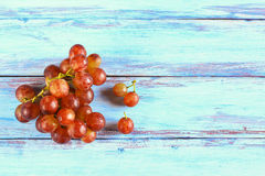 Fresh red grape on wooden table. Close up fresh red grape on wooden table top view with copy space Royalty Free Stock Photography